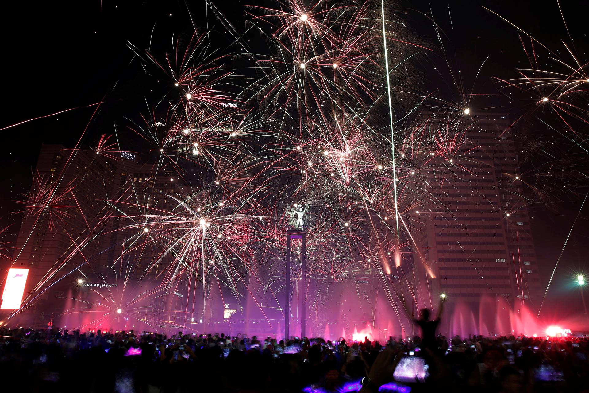 People watch fireworks explode around the Selamat Datang Monument during New Year's Eve celebrations in Jakarta, Indonesia December 31, 2016. REUTERS/Beawiharta