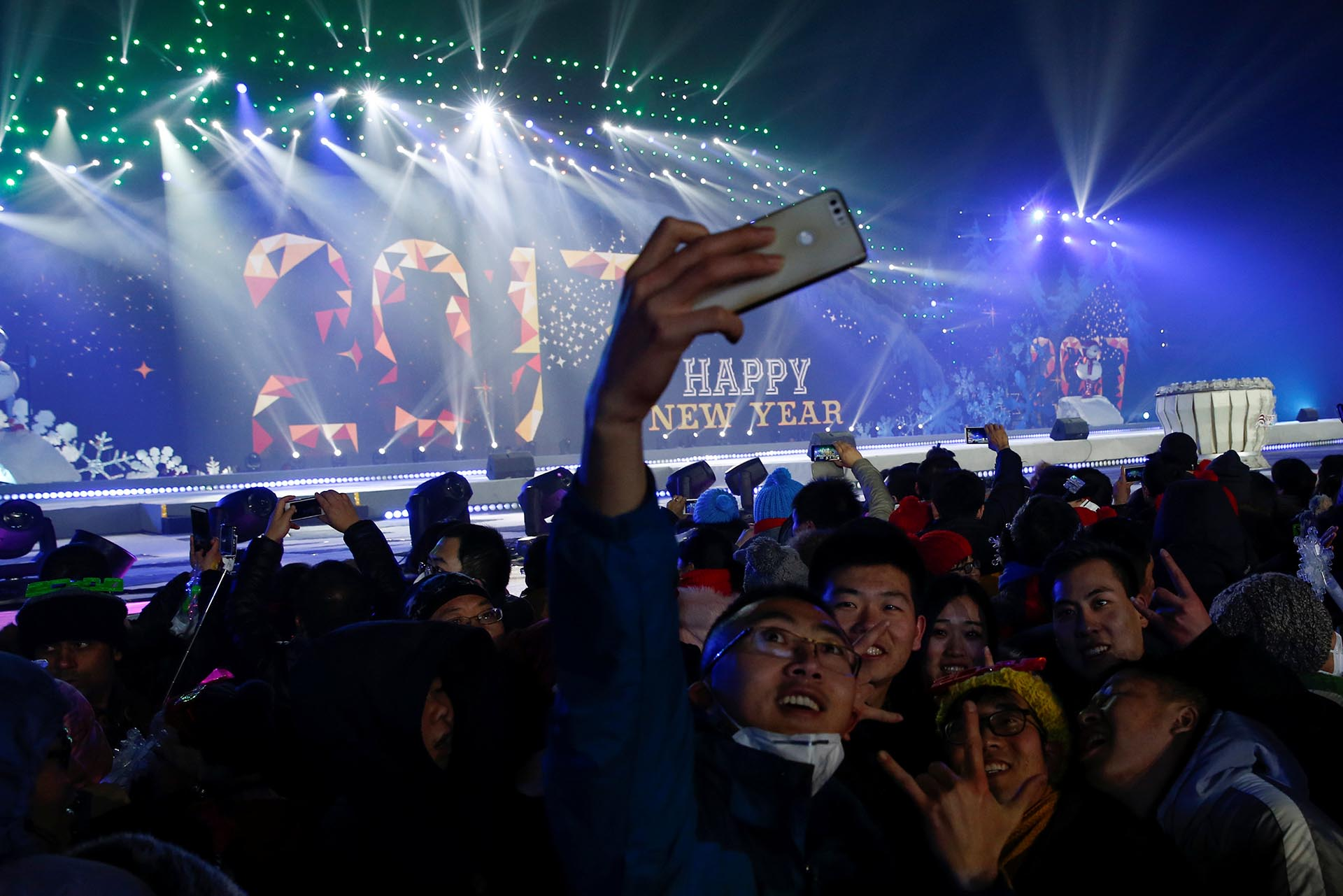 People pose for pictures as they attend a New Year's Eve countdown event in Beijing, China, December 31, 2016. REUTERS/Thomas Peter